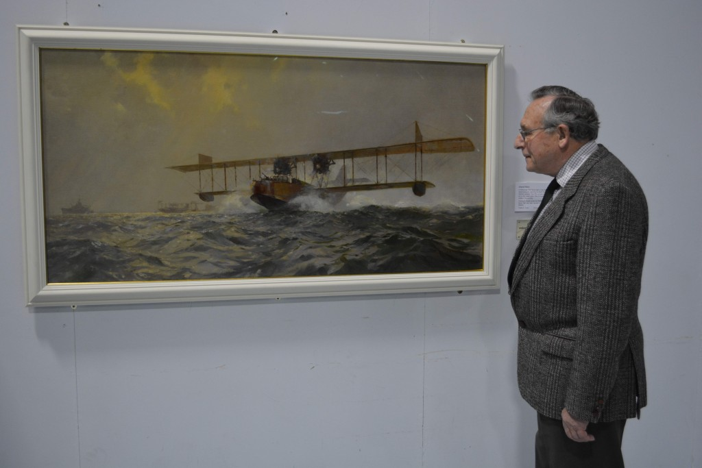 The framed picture, now on display in the Fleet Air Arm Museum, is admired by the Society's Treasurer, Gordon Johnson.